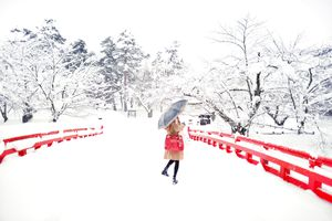 A woman standing on a bridge covered in snow with trees all around.