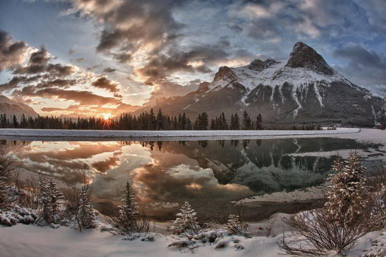 Sun rises above mountain lake, after snowfall