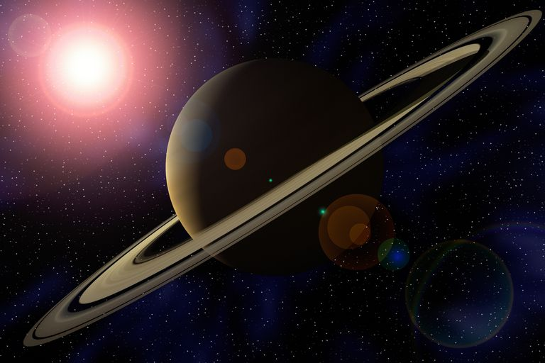 Planet Saturn with sun creating flare in background.