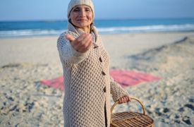 Woman beckoning on beach with picnic basket
