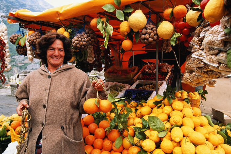 Street merchant standing in front of colorful fruit stall on Amalfi Coast, Italy.