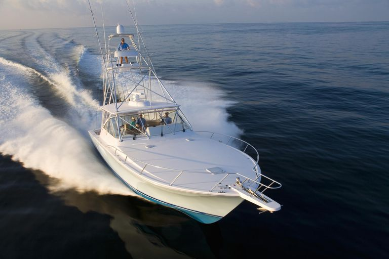 A sportfish boat with tower is underway at high speed