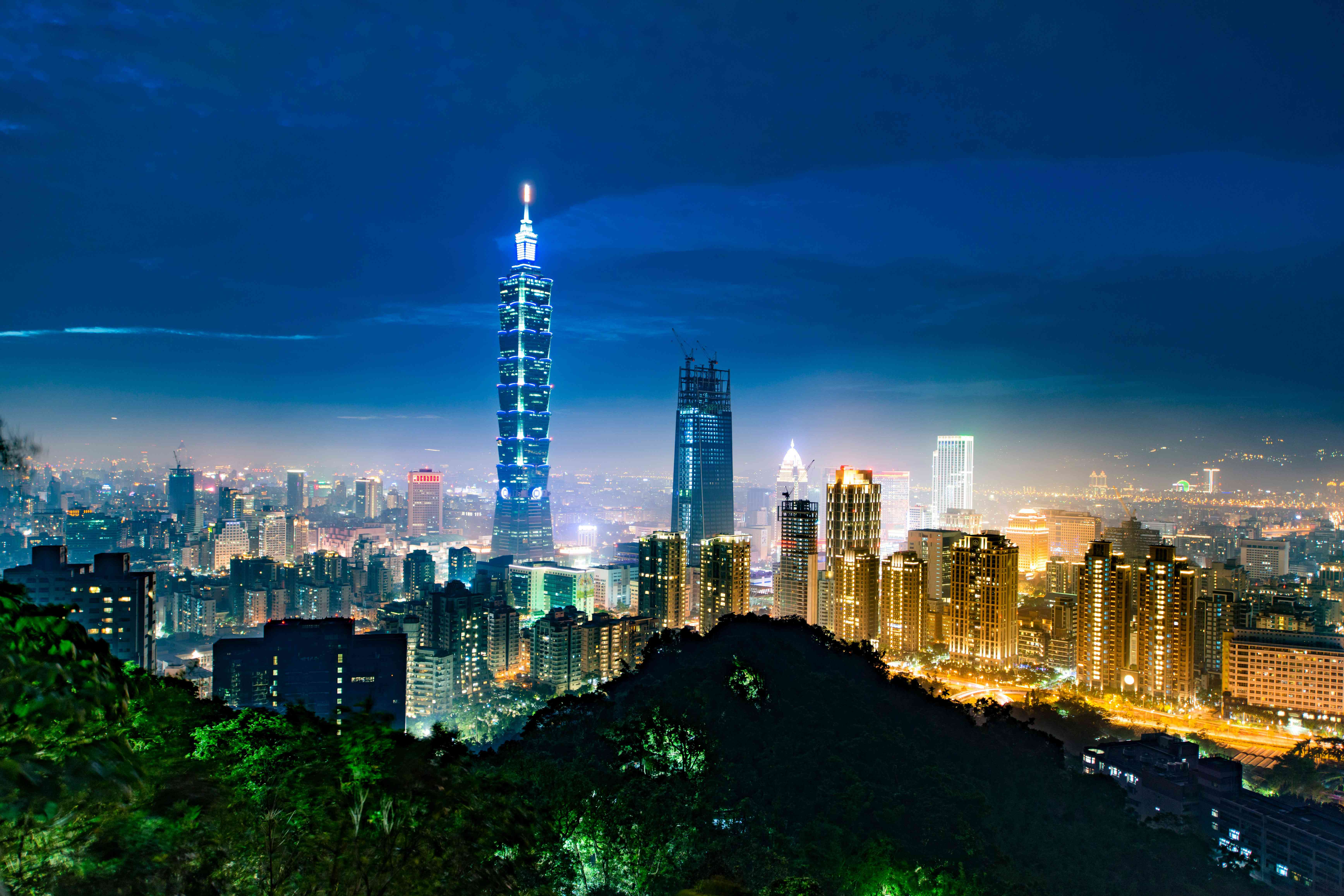 The dramatic lights of Taiwan's capital city, Taipei, surrounding the immense and iconic skyscraper Taipei 101