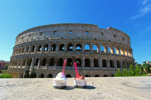 Two cups of ice cream sitting on a ledge in front of the Colosseum in Rome on a sunny day.