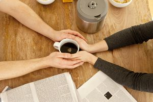 A Couple Holds Hands Over a Cup of Coffee