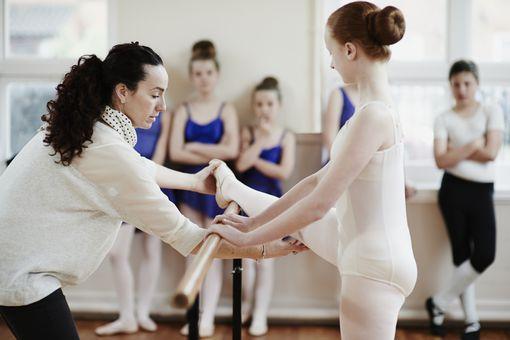 Ballet teacher helping dancer in dance studio