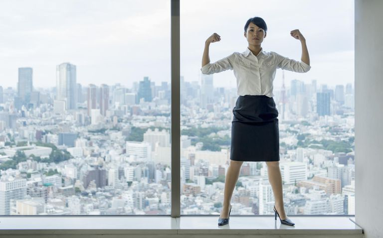 Business woman flexing muscles with city view.