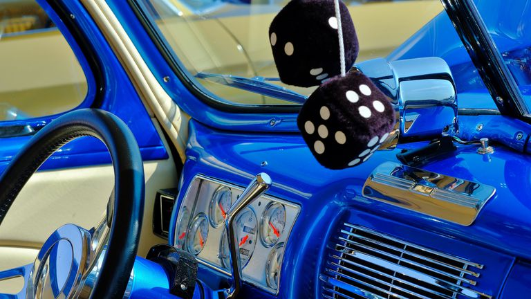 Fuzzy dice hang in a classic car