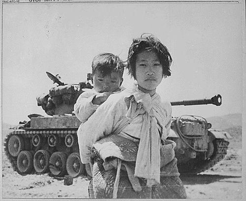 Korean brother and sister stand near a defunct tank, Haeng-ju, Korea. June 9, 1951.