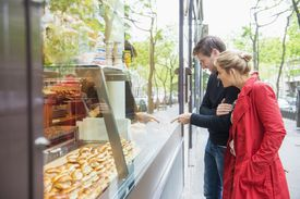 Couple looking at French pastries through window