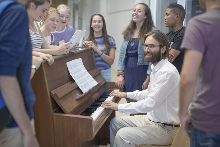 Teacher with group of students standing around piano singing