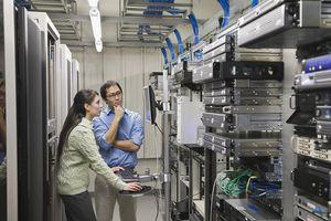 Coworkers working in computer server room