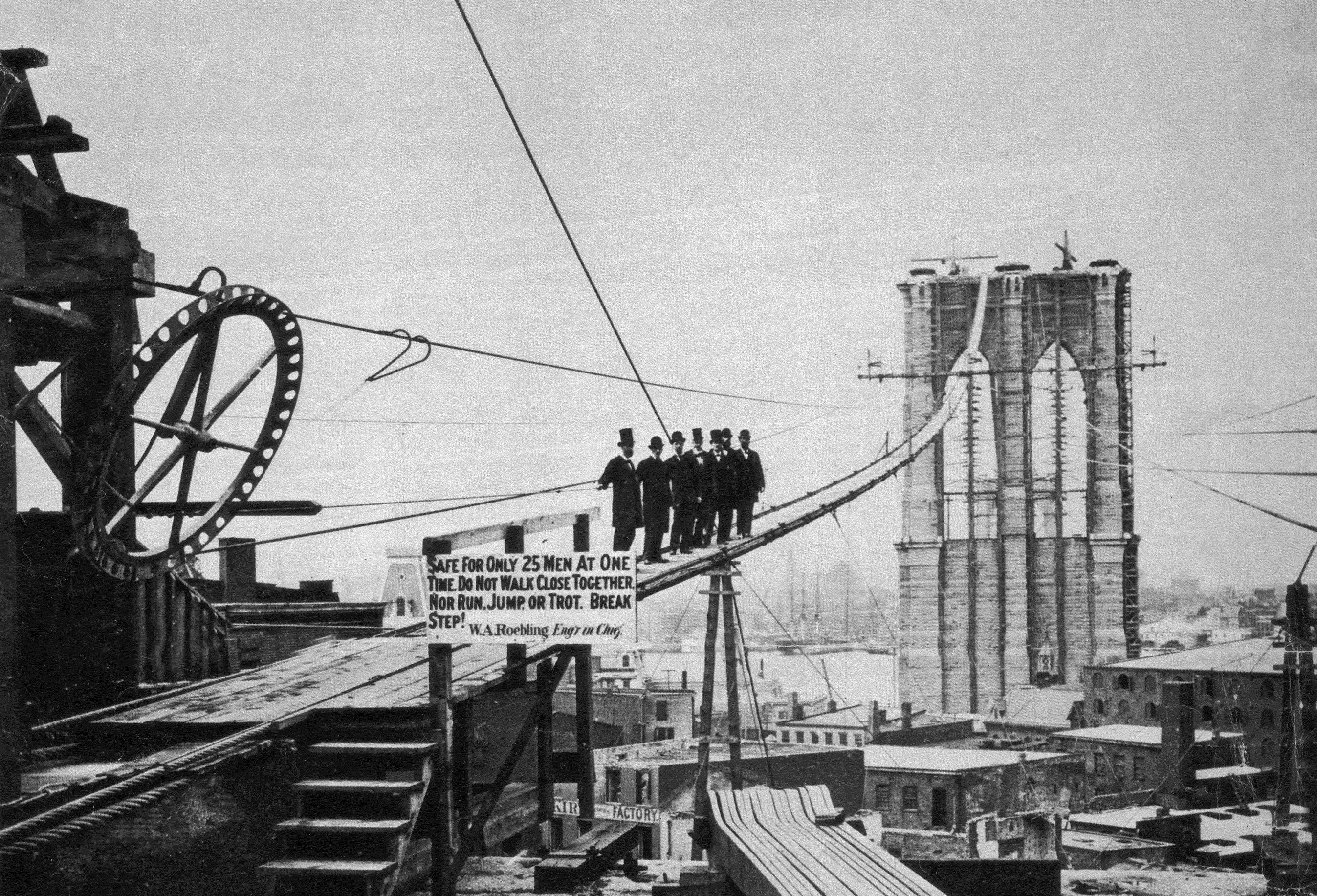 Photograph of men on catwalk during Brooklyn Bridge construction.