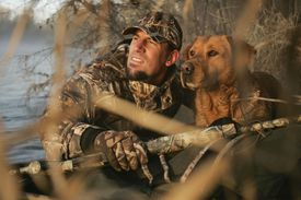 Waterfowl Hunter In Boat With Yellow Rusty Lab