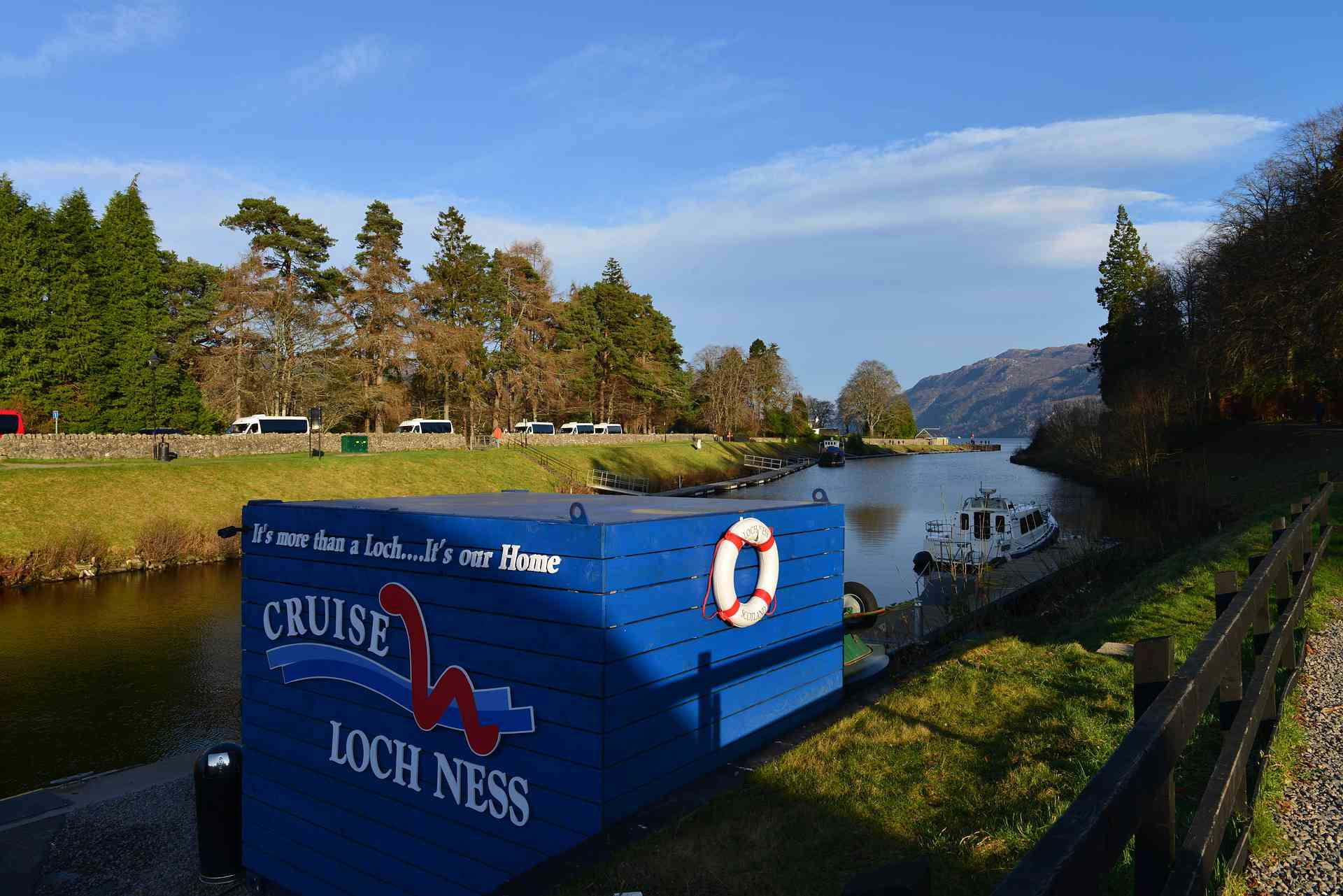 A Loch Ness tour boat docked at the lake on a bright, sunny day.