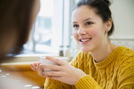 Women talking and drinking cappuccino in cafe