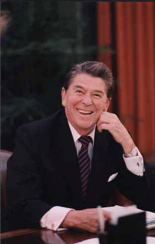 Picture of President Ronald Reagan posing at his oval office desk in 1984.