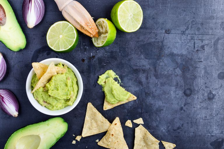 Homemade avocado guacamole dip with fresh ingredients on gark grey background with copy space