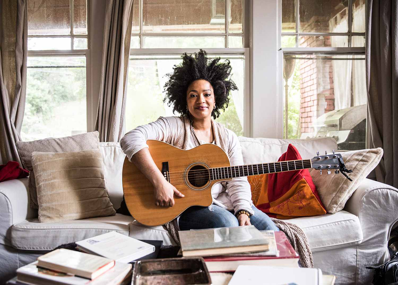 Woman playing guitar at home.