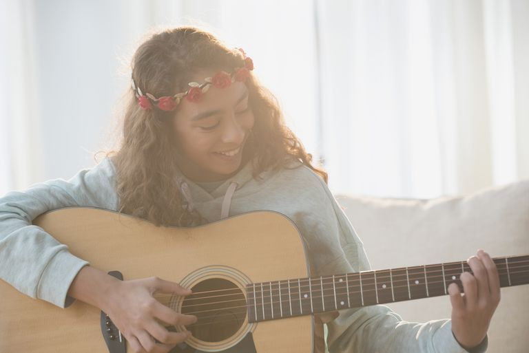 Mixed Race girl wearing flower headband playing guitar