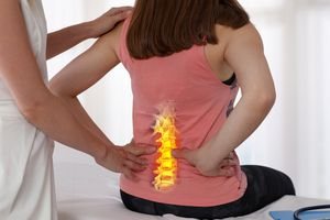 Woman suffering from low back during medical exam