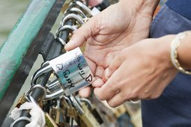 Couples' hand holding lock with their names on it on bridge in France