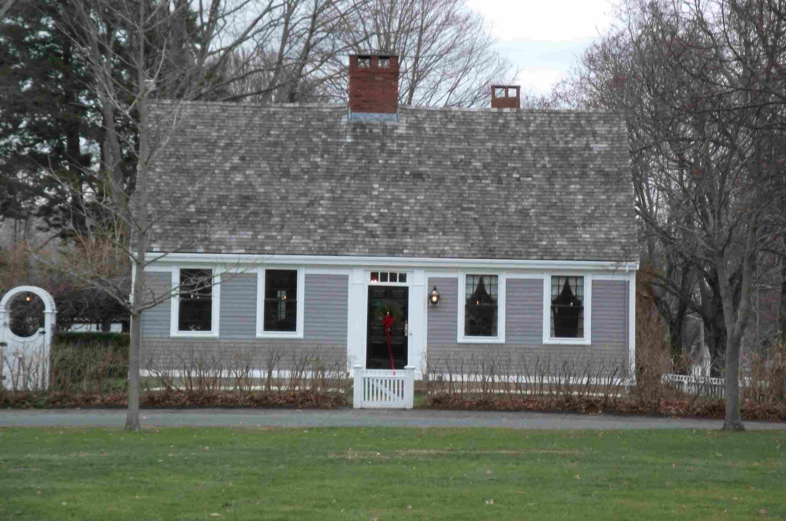 petite maison, toit en pente raide sur la façade, la cheminée centrale, porte centre, deux fenêtres de chaque côté de la porte près de l'avant-toit, garniture blanc et gris clair bardage
