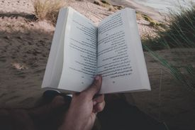 Hand holding a book on a beach in the daytime.