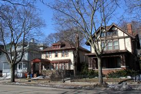 Suburban American street with three houses of various revival stylings close together and close to the sidewalk