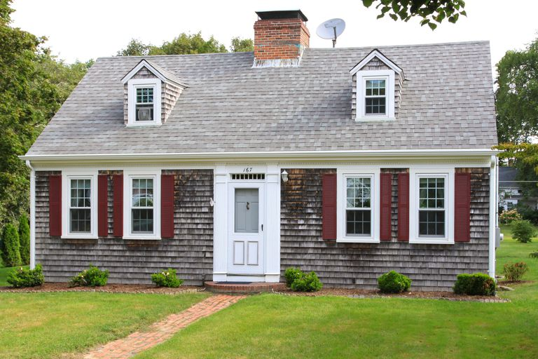 New England House with grey shingles, two small dormers without shutters, red shutters on four first-floor windows, dish antenna on roof