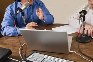 Two businessmen sitting at a table recording a podcast