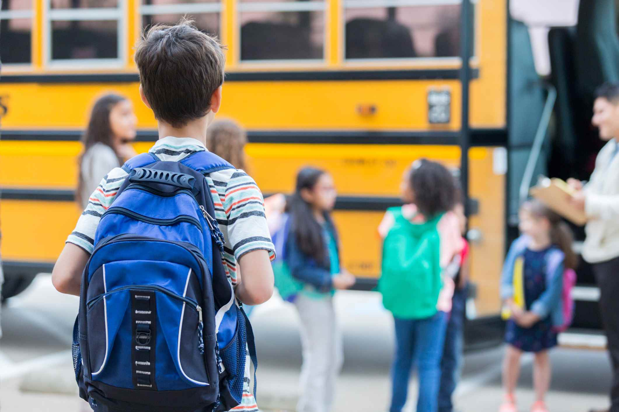 Niño esperando para subir al bus escolar