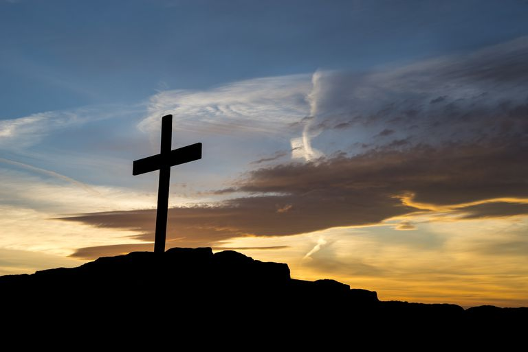 Wooden cross on a hilltop at sunset