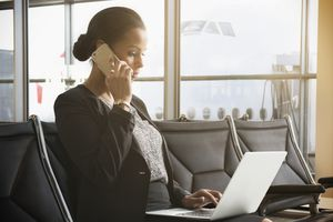 African-American businesswoman working on laptop in airport