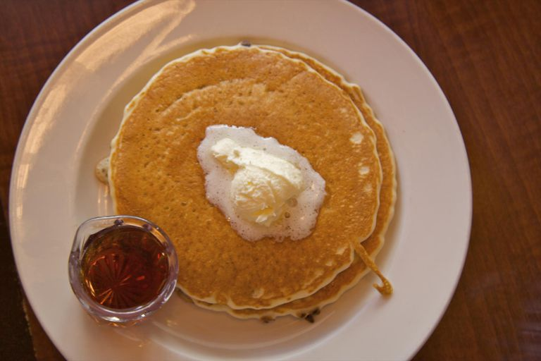 Pancakes, butter and jam on white plate