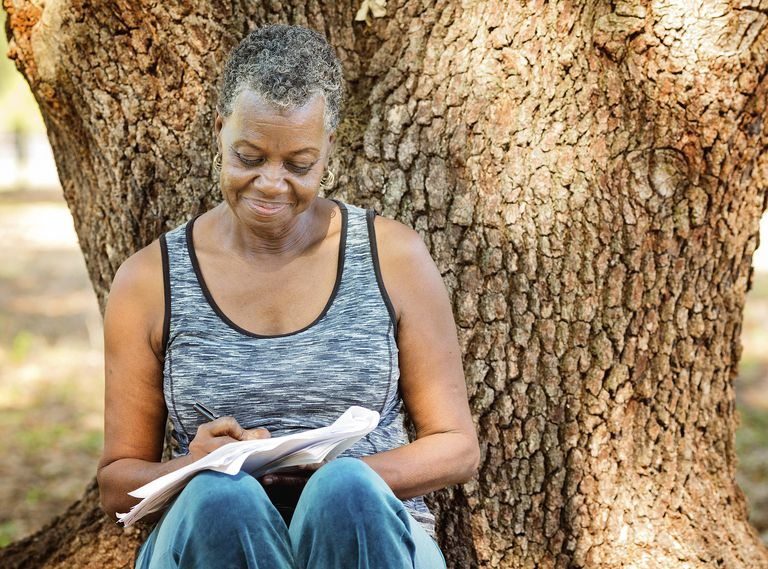 woman writing next to tree