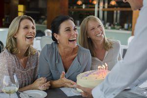 Man handing birthday cake to women