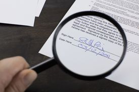 Magnifying glass pointed at a signature on a page