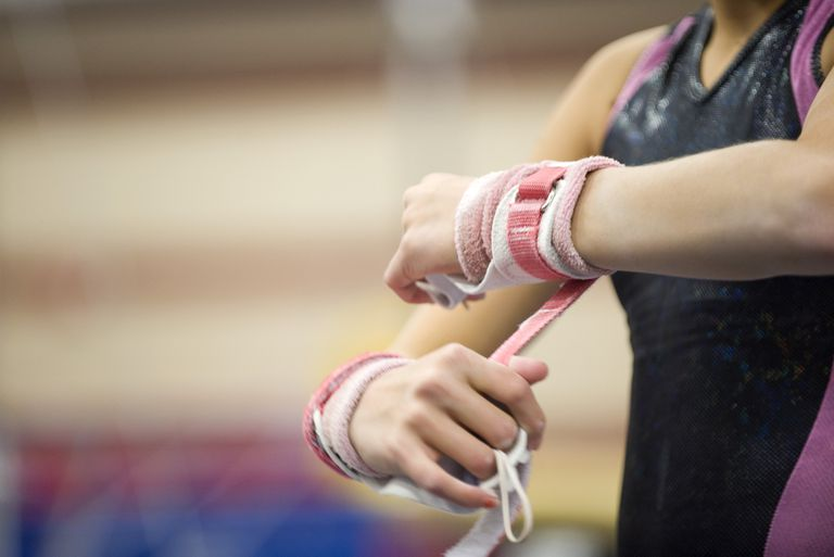 Female gymnast wrapping wrists in preparation, cropped