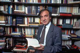 Elie Wiesel Standing Amongst Bookshelves