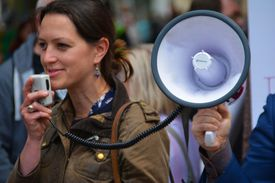 Woman speaking into a bullhorn.