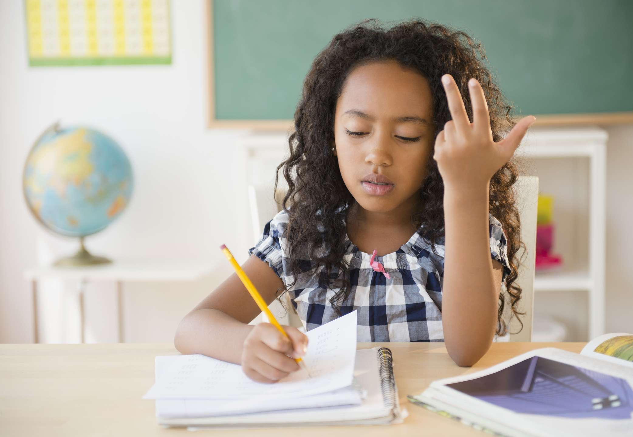 young girl counting on fingers in classroom