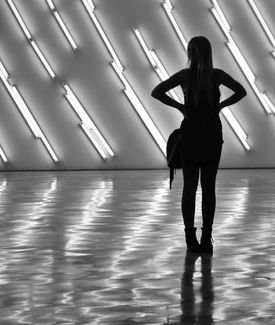 A woman silhouetted in shadows by fluorescent lights