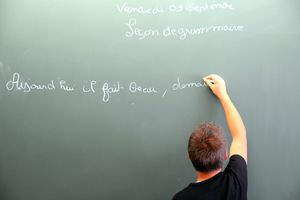 A boy works out a French grammar lesson on the chalkboard