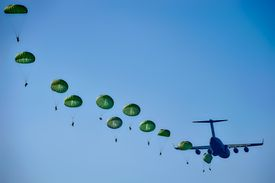 Army Rangers being dropped from an airplane against a perfect blue sky.