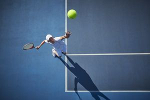 Overhead view of young male tennis player playing tennis, serving the ball on sunny blue tennis court