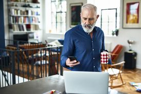 Senior male checking his phone while standing in front of his laptop at home.