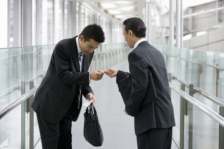Two businessmen exchanging business cards and bows