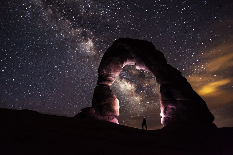 Person standing under a stone arch surrounded by the night sky.