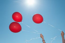 Red balloons against a blue sky